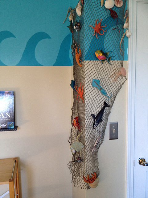 He loves to collect those plastic sea animals and I used a fishing net to display them on this corner in his room.